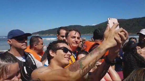 Bolsonaro passeia e tira foto com apoiadores em praia do litoral paulista